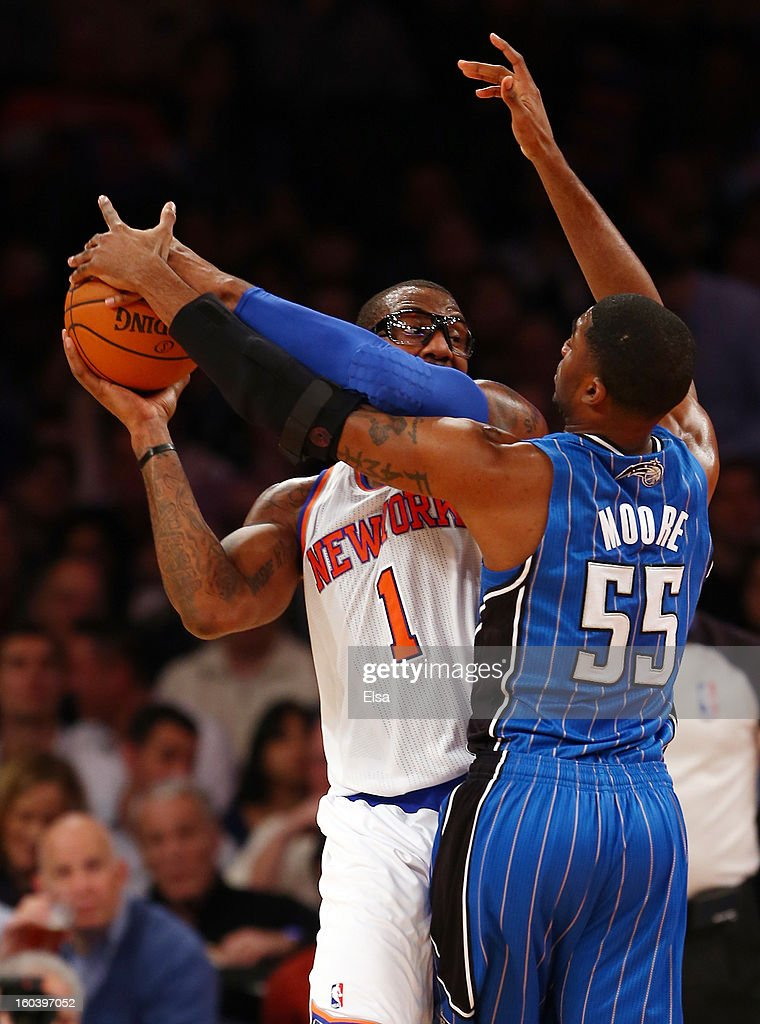 Amar'e Stoudemire #1 of the New York Knicks tries to pass as E'Twaun Moore #55 of the Orlando Magic defends on January 30, 2013 at Madison Square Garden in New York City.
