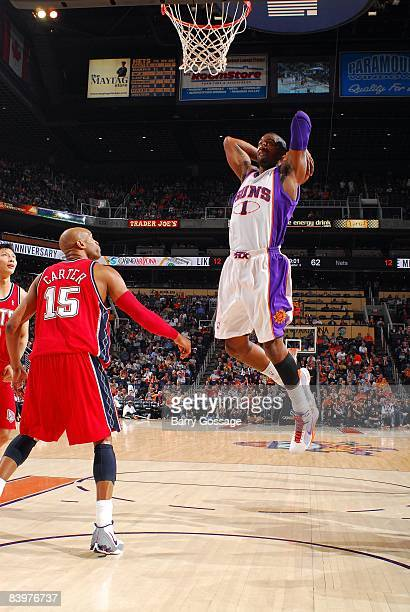 Amare Stoudemire of the Phoenix Suns dunks against Vince Carter of the New Jersey Nets during the game at US Airways Center on November 30 2008 in...