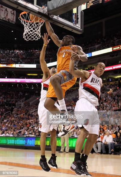 Amar'e Stoudemire of the Phoenix Suns slam dunks the ball between Juwan Howard and Jerryd Bayless of the Portland Trail Blazers during the NBA game...