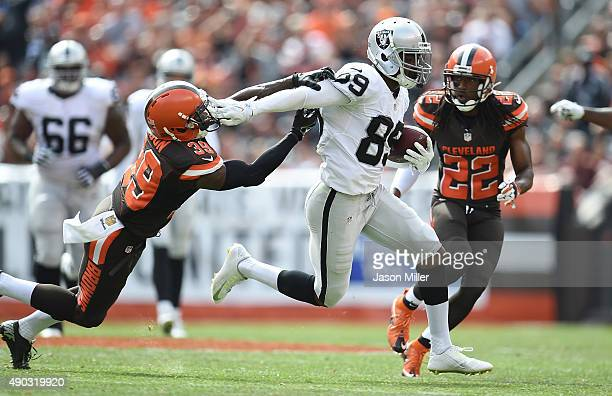 Amari Cooper of the Oakland Raiders stiff arms Tashaun Gipson of the Cleveland Browns during the second quarter at FirstEnergy Stadium on September...