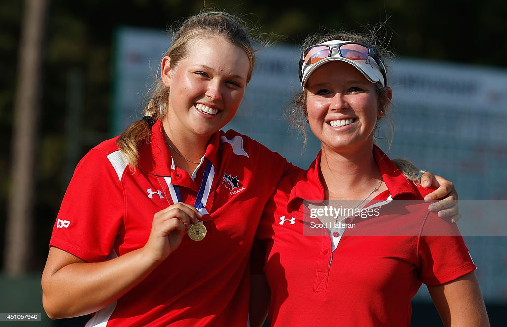 Amateur Brooke Henderson of Canada poses with the Low Amateur medal alongside her sister/caddie Brittany after the final round of the 69th US Women's...