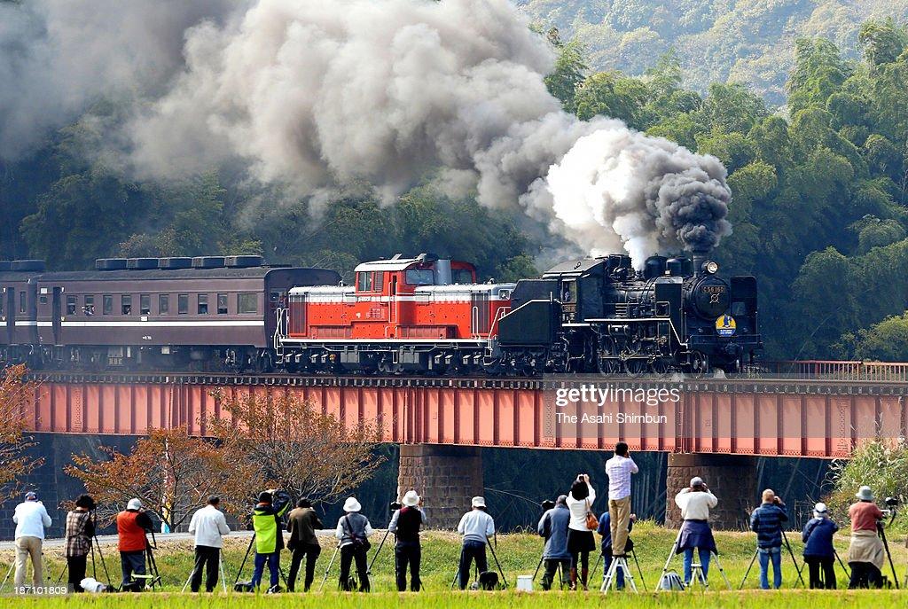 Amateur photographers take photographs of a steam locomotive, named 'SL Ganbaro Yamaguchi-Tsuwano' on November 2, 2013 in Yamaguchi, Japan. The train operator Western Japan Railway (JR West) is operating the train between Shin Yamaguchi and Jifuku Station on November 2 and 3, December 21, January 1 to 3