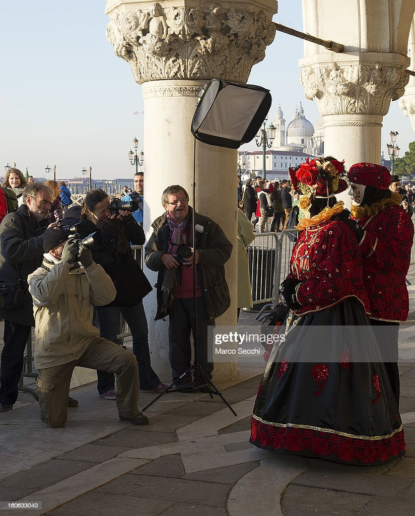 Amateur photographers take pictures of a couple dressed in costume while they pose in Saint Mark's Square during the Venice Carnival 2013 on February 4, 2013 in Venice, Italy. The 2013 Carnival of Venice runs from January 26 - February 12 and includes a program of gala dinners, parades, dances, masked balls and music events.