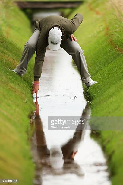 Amateur Rory McIlroy of Northern Ireland collects his golf ball from the burn on the ninth hole during the second round of The 136th Open...