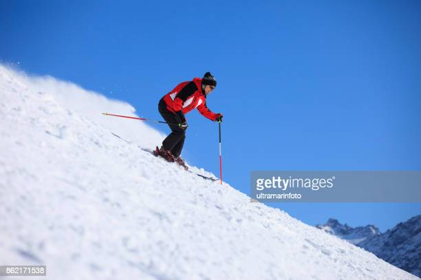 Amateur Winter Sports  alpine skiing. Men , snow skiers, enjoying on sunny ski resorts.  High mountain snowy landscape. Dolomite mountain range, Alps. It is located in the Italiy.
