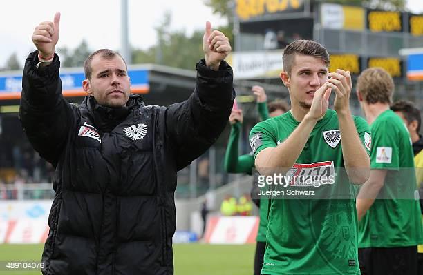 Amaury Bischoff and Chris Philipps of Muenster applaud after the Third League match between Preussen Muenster and Fortuna Koeln at Preussenstadion on...