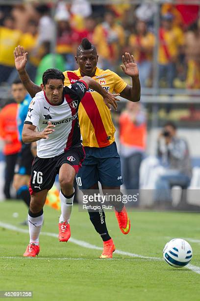 Amaury Ponce of Atlas runs for the ball as Duvier Riascos of Morelia tries to avoid the foul during a match between Morelia and Atlas as part of 2nd...