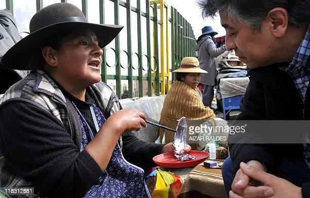 Amauta Aymara fortune teller Ninfa Gutierrez reads the fortune of a man on lead on July 2 2011 in El Alto 12 Km west of La Paz After the winter...