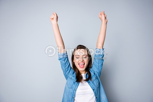 Amazed brunette young business woman in casual shirt is gesturing victory with her raised hands, she is shocked, extremely happy, with closed eyes, beaming smile, open mouth  on  grey background : Stock Photo