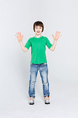 Emotional full length pirtrait of surprised boy showing his palms at studio on white background. Funny innocent child displaying empty hands, posing on camera, copy space