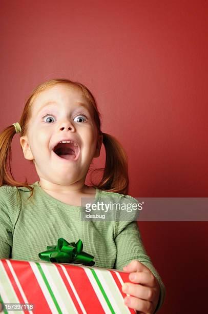 Sorprendido niña con regalo de navidad