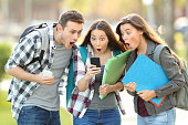Three amazed students checking on line content on a smart phone in the street