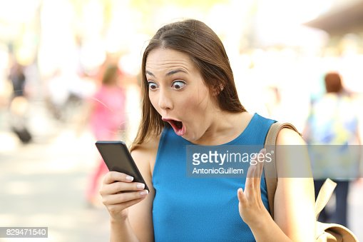 Amazed woman receiving shocking news : Stock Photo