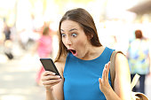 Amazed woman receiving shocking news on a smart phone on the street