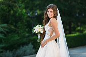 Amazing bride in beautiful white wedding dress hold bouquet of flowers in her hands. Concept of clothes and floristics.
