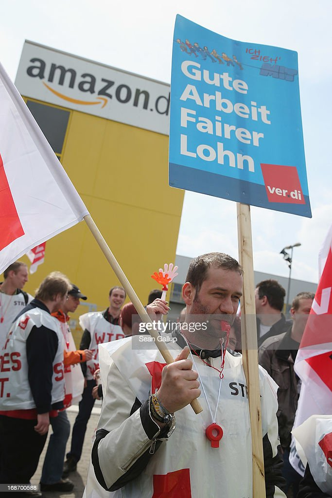 Amazon workers wearing bibs of the ver.di service industry labour union, including one with a sign that reads: 'Good Work, Fair Wages,' stand vigil while striking outside the Amazon warehouse on May 14, 2013 in Leipzig, Germany. Approximately 5,000 Amazon workers at the Leipzig and Bad Hersfeld warehouses have gone on a 24-hour strike in an effort to press the company harder in their ongoing labour dispute over wages and work hours.