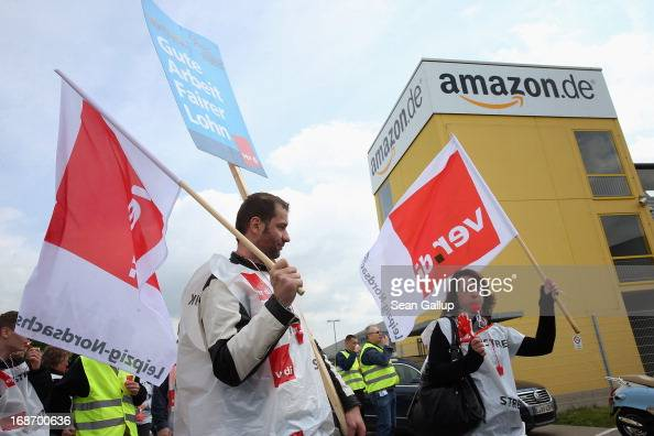 Amazon workers wearing bibs of the verdi service industry labour union stand vigil while striking outside the Amazon warehouse on May 14 2013 in...