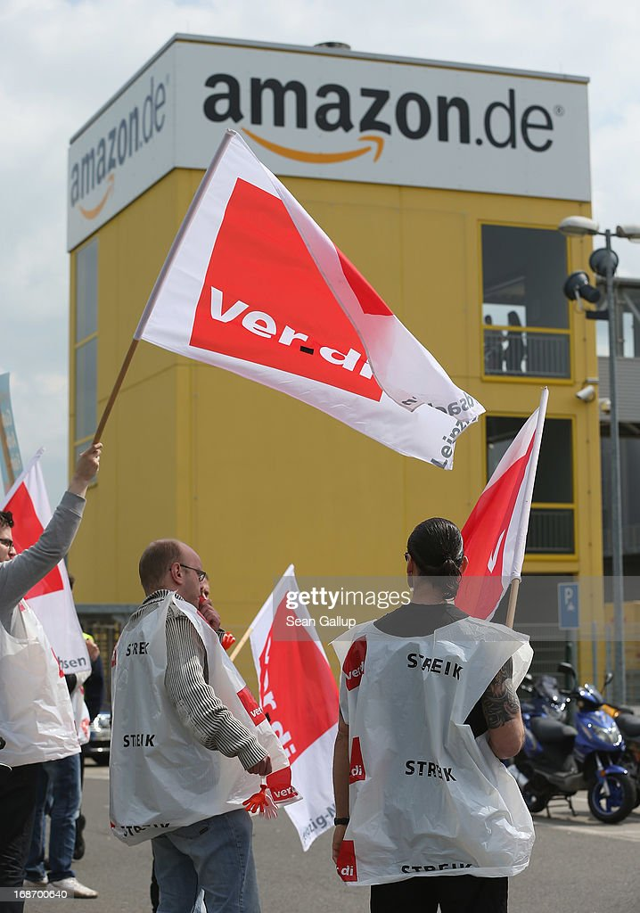 Amazon workers wearing bibs of the ver.di service industry labour union stand vigil while striking outside the Amazon warehouse on May 14, 2013 in Leipzig, Germany. Approximately 5,000 Amazon workers at the Leipzig and Bad Hersfeld warehouses have gone on a 24-hour strike in an effort to press the company harder in their ongoing labour dispute over wages and work hours.