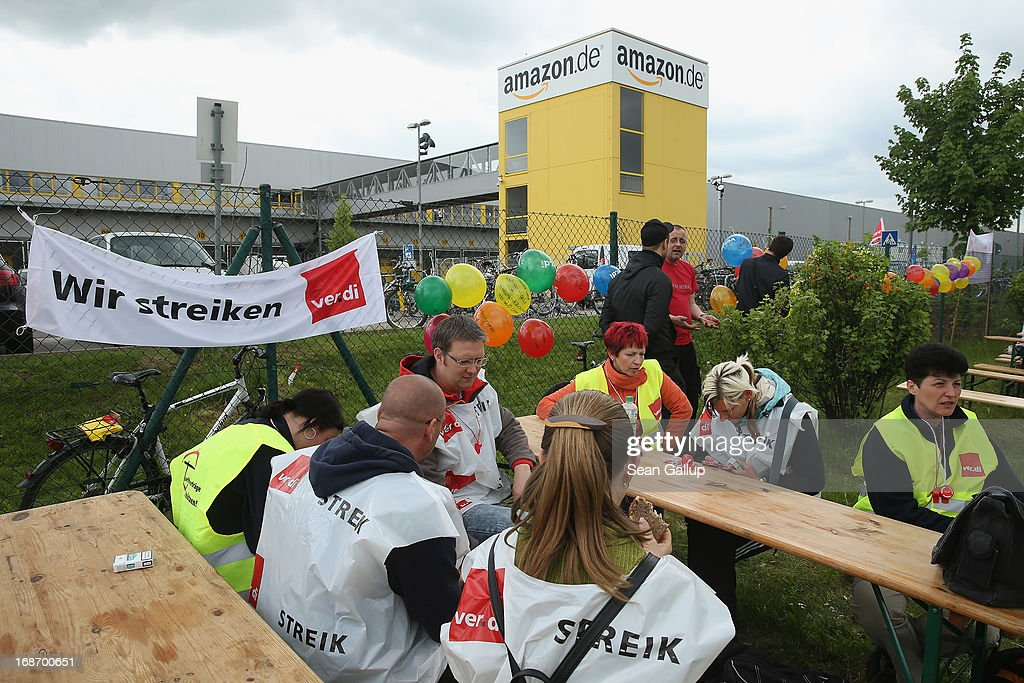 Amazon workers wearing bibs of the ver.di service industry labour union hold vigil while striking outside the Amazon warehouse on May 14, 2013 in Leipzig, Germany. Approximately 5,000 Amazon workers at the Leipzig and Bad Hersfeld warehouses have gone on a 24-hour strike in an effort to press the company harder in their ongoing labour dispute over wages and work hours.