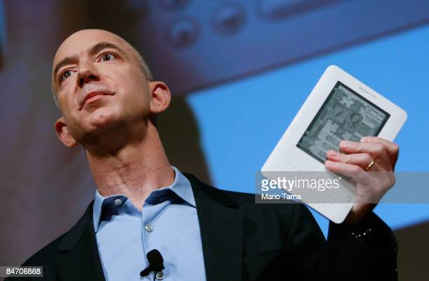 Amazoncom founder and CEO Jeffrey P Bezos holds the new Amazon Kindle 20 at an unveiling event at the Morgan Library Museum February 9 2009 in New...