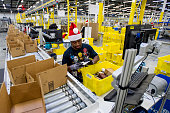 Amazoncom Inc employees load boxes with orders at the company's fulfillment center ahead of Cyber Monday in Tracy California US on Sunday Nov 30 2014...