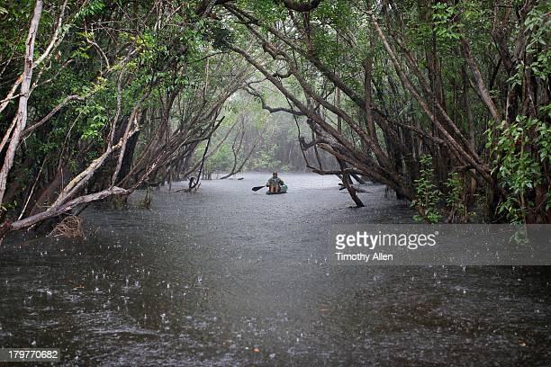 Amazonian woman rows Rio Negro river in rain