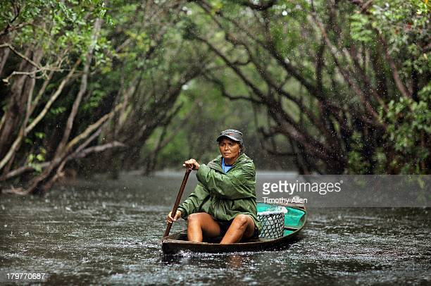 Amazonian woman rows Rio Negro river in rain