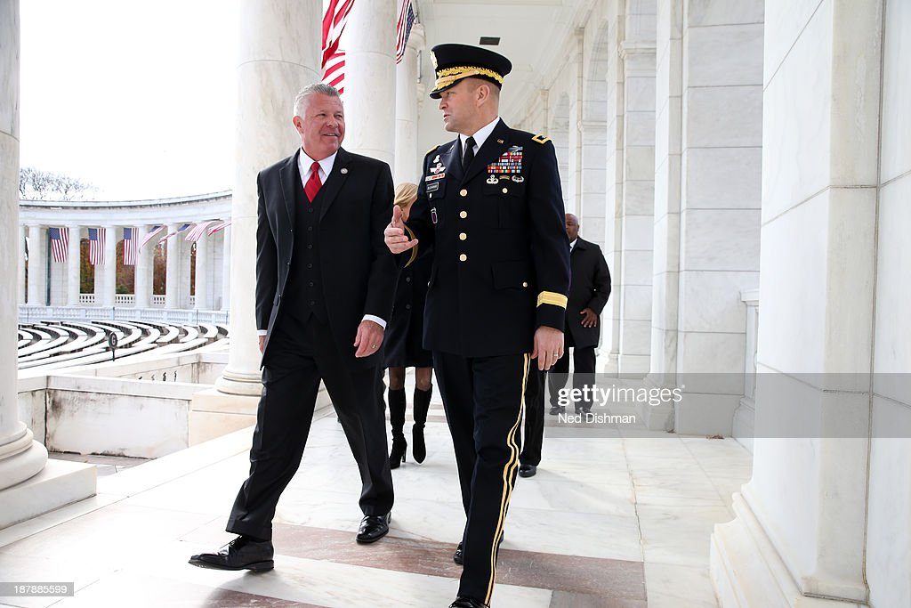 NBA ambassador Bob Delaney and Major General Jeffrey S. Buchanan walk together prior to a wreath laying ceremony at Arlington National Cemetery on November 13, 2013 in Washington, DC.