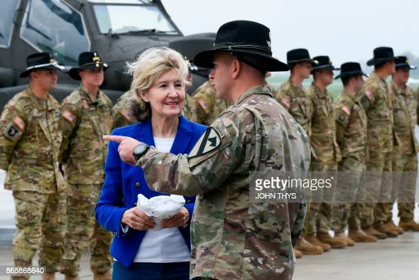 Ambassador Kay Bailey Hutchison talks with US colonel Phillip Baker as she reviews troops and equipment of the US Army 1st Cavalry Brigade 1st...