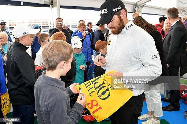 Ambassador Louis Oosthuizen of South Africa signs autographs as he participates in the Bags 4 Birdies Campaign during previews ahead of the 145th...