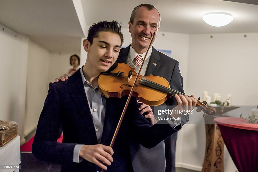 U.S. Ambassador Philipp Murphy (R) poses behind the violinist David Solomon (L), as he visits a Catholic charity housing project home mostly to Roma from Romania and Bulgaria in Harzer Strasse on April 8, 2013, in Berlin, Germany. The Catholic real estate group, called the Aachener Sieldungs- und Wohnungsgesellschaft, bought the complex of buildings with over 100 apartments in 2011, and through the active input of the Roma families living there turned it into a success story of progressive living and immigration policy. The Harzer Strasse facility offers German language classes, urban adaptation and other workshops designed to help the Roma families integrate successfully into life in Germany. Germany, like many countries in western Europe, has experienced a large influx of Roma from Romania and Bulgaria in recent years.