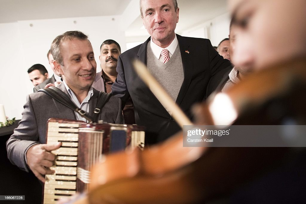 U.S. Ambassador Philipp Murphy (C) stays between the violinist David Solomon (R) and the accordionist Eugen Stoika (L), as he visits a Catholic charity housing project home mostly to Roma from Romania and Bulgaria in Harzer Strasse on April 8, 2013, in Berlin, Germany. The Catholic real estate group, called the Aachener Sieldungs- und Wohnungsgesellschaft, bought the complex of buildings with over 100 apartments in 2011, and through the active input of the Roma families living there turned it into a success story of progressive living and immigration policy. The Harzer Strasse facility offers German language classes, urban adaptation and other workshops designed to help the Roma families integrate successfully into life in Germany. Germany, like many countries in western Europe, has experienced a large influx of Roma from Romania and Bulgaria in recent years.