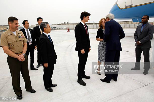 US Ambassador to Japan Caroline Kennedy and her son Jack Schlossberg greet US Secretary of State John Kerry upon his arrival at Iwakuni Marine Corps...