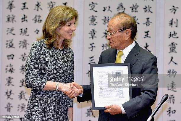 US Ambassador to Japan Caroline Kennedy hands a copy of an application for a Japanese visa completed by former President John F Kennedy her late...