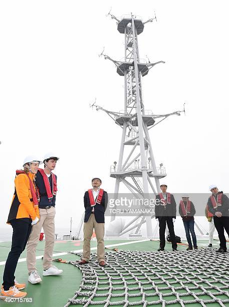 US Ambassador to Japan Caroline Kennedy stands next to her 21yearold son John Schlossberg as she speaks to journalists on the heliport of a floating...