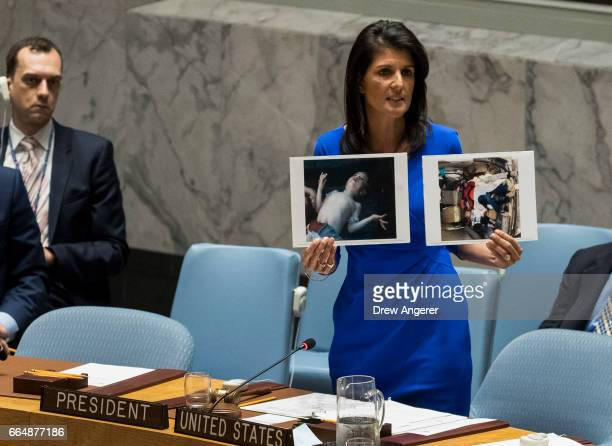 S Ambassador to the United Nations Nikki Haley holds up photos of victims of the Syrian chemical attack during a meeting of the United Nations...