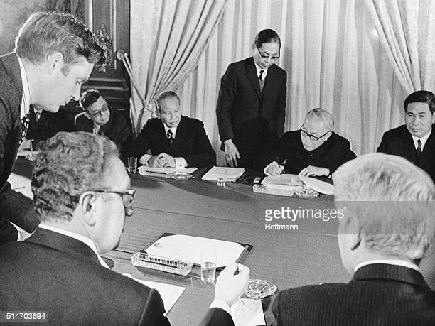 Ambassador William H Sullivan and Xuan Thuy watch as Dr Henry Kissinger and Le Duc Tho initial the Paris Peace Accords in Paris on January 23 1973