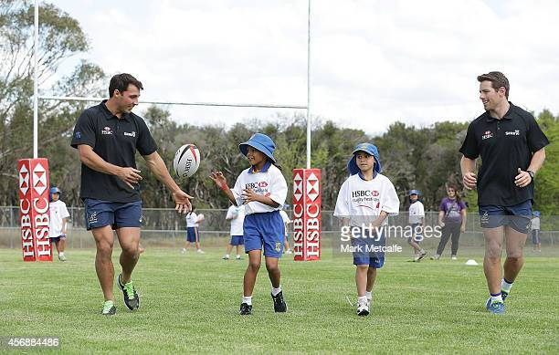 HSBC ambassadors Nick Phipps and Bernard Foley perform a passing drill with local school children during the HSBC Rugby Festival at Nepean Rugby Park...