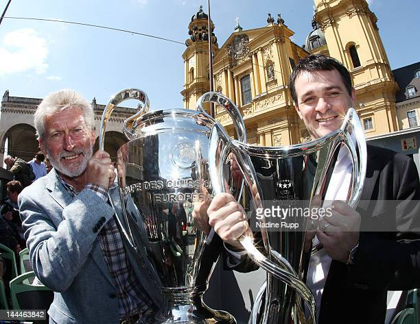 UEFA ambassadors Paul Breitner and Willy Sagnol pose with the men and women's Champions League the trophies in front of the with Feldherrenhalle and...