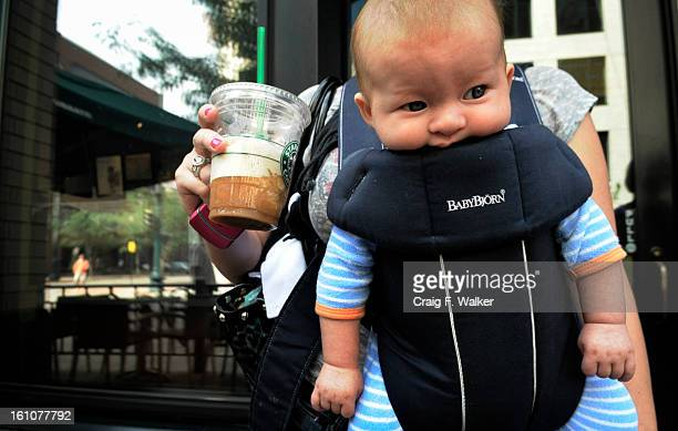 FEATURE_080708_CFW Amber Ekstrom of Denver holds her beverage in hand and her 3 month old son Becket in a pouch as she departs Starbuck at 16th and...
