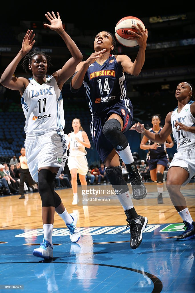 Amber Harris of the Minnesota Lynx tries to defend a layup against Tan White of the Connecticut Sun during the WNBA preseason game on May 21 2013 at...