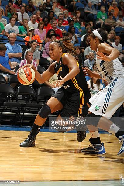 Amber Holt of the Tulsa Shock dribbles past Maya Moore of the Minnesota Lynx during the WNBA game on July 12 2012 at Target Center in Minneapolis...