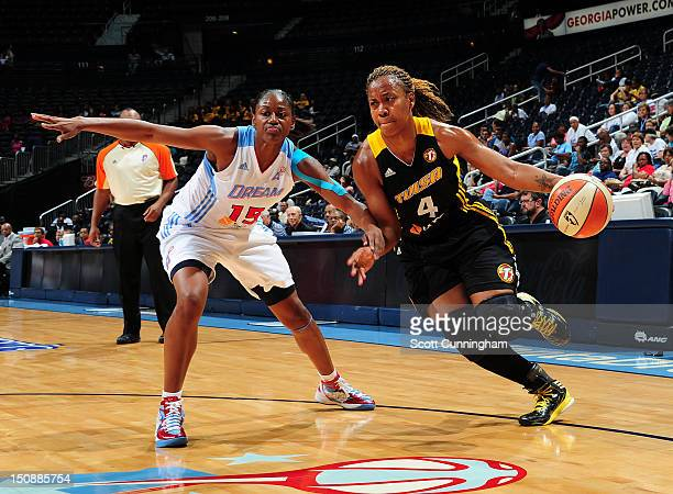 Amber Holt of the Tulsa Shock drives against Tiffany Hayes of the Atlanta Dream at Philips Arena on August 28 2012 in Atlanta Georgia NOTE TO USER...