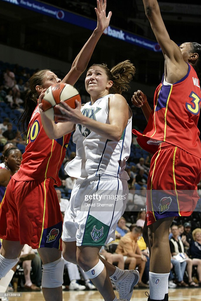 Amber Jacobs of the Minnesota Lynx drives to the basket between Kayte Christensen and Angelina Williams of the Phoenix Mercury on June 22 2005 at the...