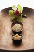 Amber sea salt, sugar scrub and orchid on wooden tray, elevated view