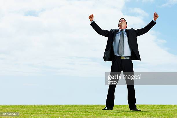 Ambitious business man standing on grass with arms outstretched