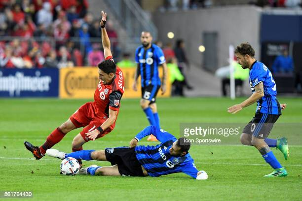 Ambroise Oyongo of Montreal Impact performs a sliding tackle on Marco Delgado of Toronto FC during the second half of the MLS Soccer regular season...