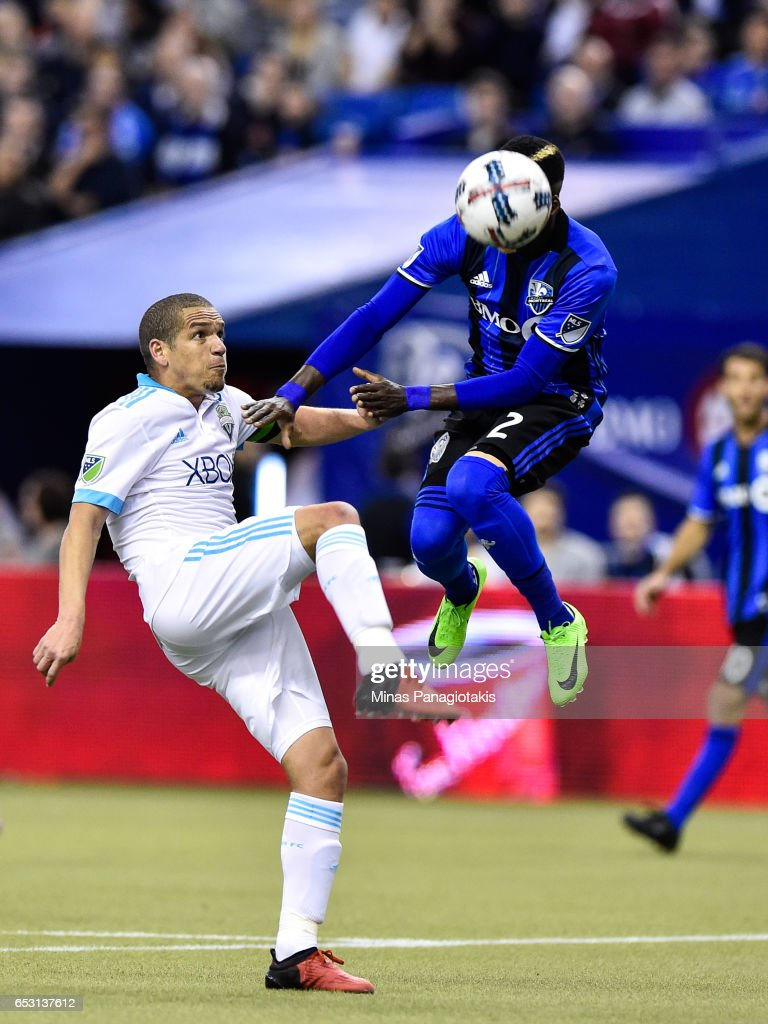 Ambroise Oyongo #2 of the Montreal Impact jumps for the ball as Osvaldo Alonso #6 of the Seattle Sounders prepares to kick during the MLS game at Olympic Stadium on March 11, 2017 in Montreal, Quebec, Canada. The Seattle Sounders FC and the Montreal Impact end up in a 2-2 draw.
