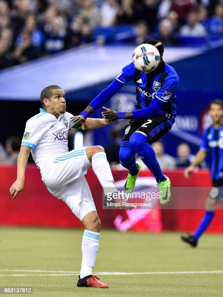Ambroise Oyongo of the Montreal Impact jumps for the ball as Osvaldo Alonso of the Seattle Sounders prepares to kick during the MLS game at Olympic...