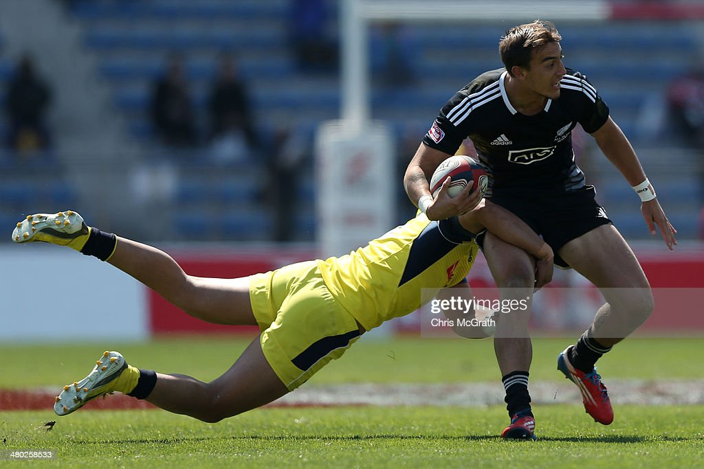 Ambrose Curtis #11 of New Zealand tries to break the tackle of Peter Schuster #5 of Australia during the Tokyo Sevens, in the six round of the HSBC Sevens World Series at the Prince Chichibu Memorial Ground on March 23, 2014 in Tokyo, Japan.